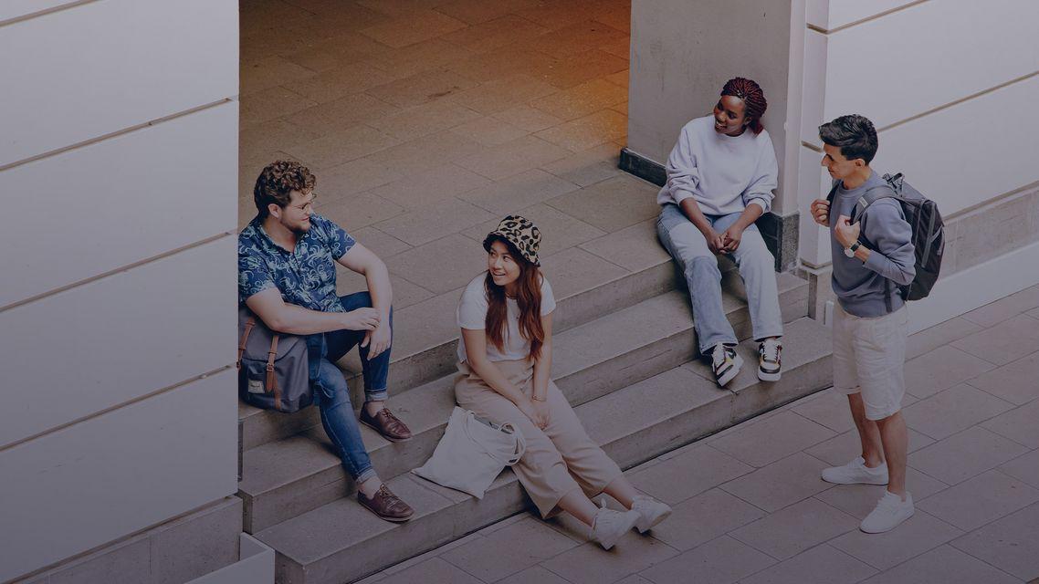 Studierende sitzen auf Treppenstufen